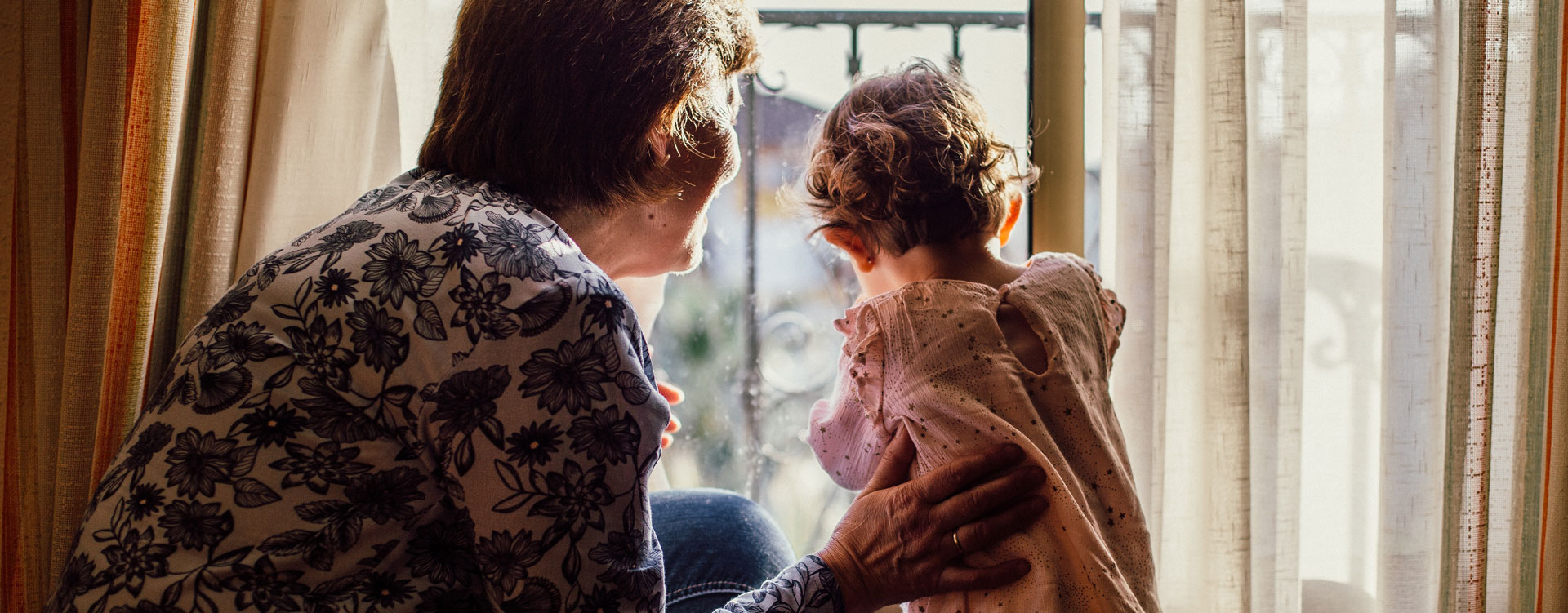 Old lady and a child looking outside window after a domestic violence