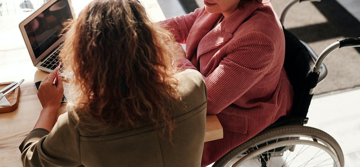 Woman on a wheelchair talking to a domestic violence helprepresentative